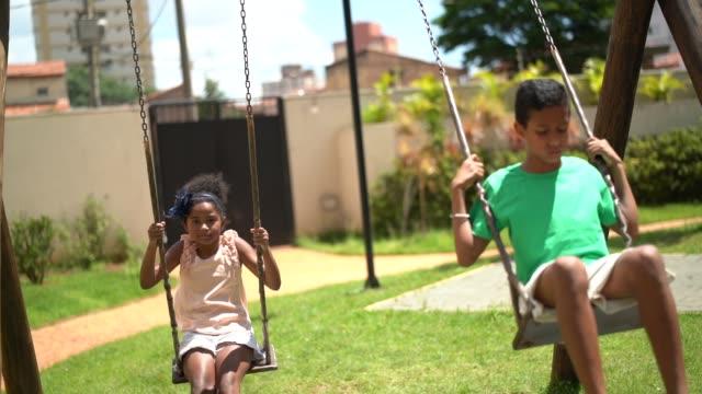 vídeos de stock, filmes e b-roll de feliz irmão balançando - swing