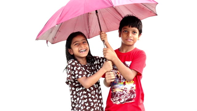 Happy siblings under the umbrella
