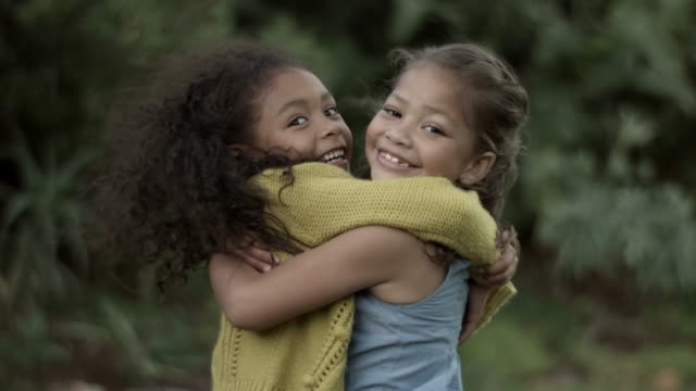 stockvideo's en b-roll-footage met happy sisters embracing in backyard - bovenlichaam