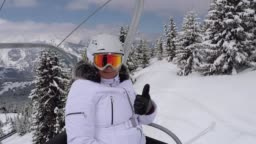 Happy Skier Climbs Up The Chair Lift To The Mountain Top And Shows Her Thumb Up
