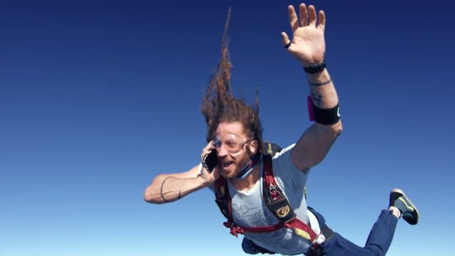 happy skydiver on his phone - skydiving stock videos & royalty-free footage