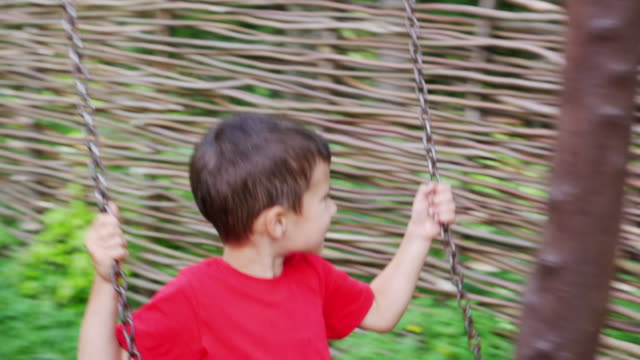 happy small boy playing on tire swing - tire swing stock videos & royalty-free footage