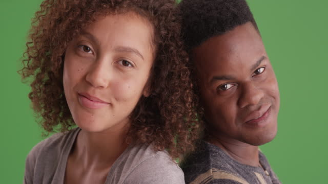 happy smiling african american man and woman lean on each other on green screen - other点の映像素材/bロール