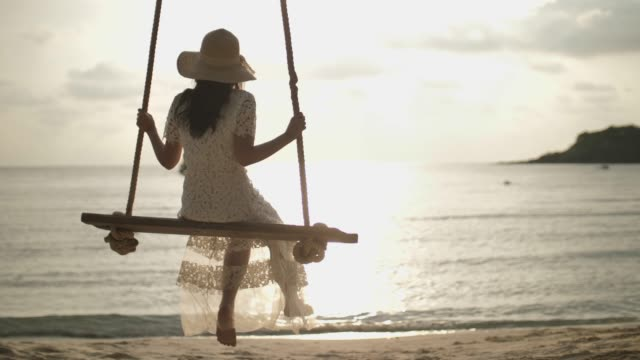 happy smiling asian woman sitting on rope swing  for relaxing dangle feet on beach with sunset - sitting stock videos & royalty-free footage