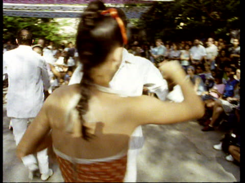 vidéos et rushes de happy smiling couple dance the rumba in sunny square as crowds watch on. woman wears orange polka dot dress and man wears white suit other dancing couples in background cuba - cuba