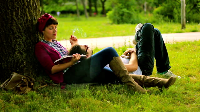 happy smiling couple lying on grass and relaxing - cigarette stock videos & royalty-free footage