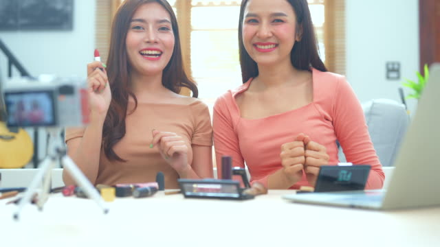 happy smiling two young asian woman or beauty blogger talking and looking to camera while recording video and waving hand, work at home concept. beauty videoblog blogging people concept. dolly shot. - tutorial stock videos & royalty-free footage