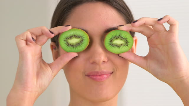 happy smiling woman making funny faces with fruit over eyes - kiwi fruit stock videos and b-roll footage