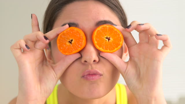 Happy smiling woman making silly faces with fruit over eyes