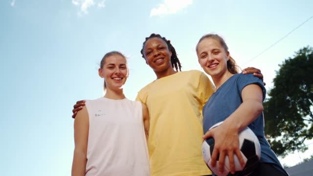vidéos et rushes de jeunes joueurs de football féminins heureux de sourire - trois personnes