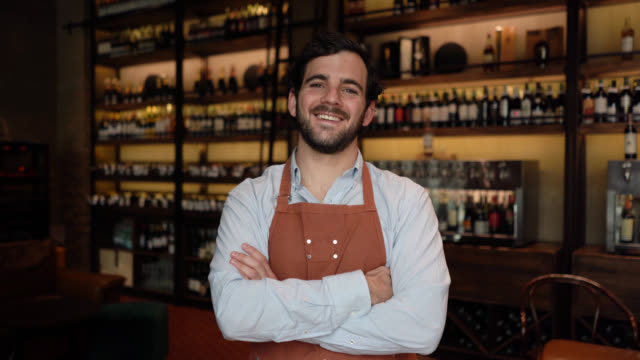 happy sommelier working at a wine bar and looking at the camera smiling while crossing arms - wine bar stock videos & royalty-free footage