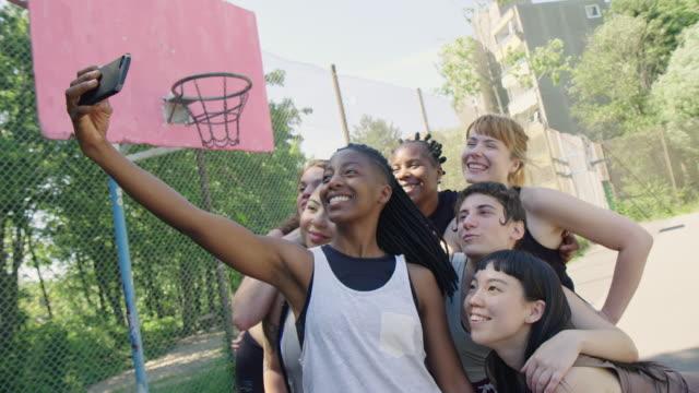 vidéos et rushes de joueurs heureux de streetball prenant le selfie sur la cour - streetball