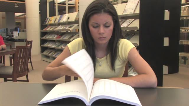 glückliche schüler in der bibliothek (hd - literatur stock-videos und b-roll-filmmaterial