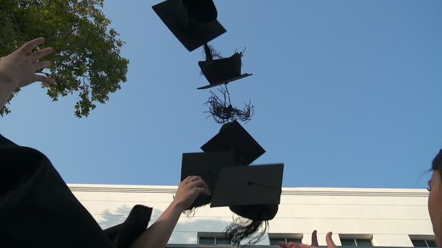 Happy students in gowns throwing mortarboards in the air.Education, graduation and people concept -