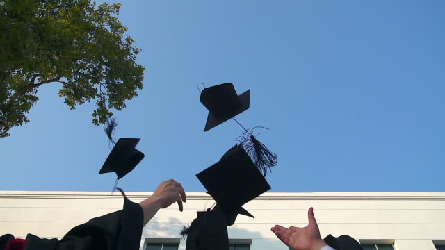 happy students in gowns throwing mortarboards in the air.education, graduation and people concept - - lanciare video stock e b–roll