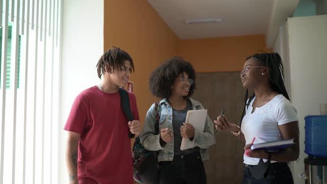 happy students talking in the school / university corridor - community college stock videos & royalty-free footage
