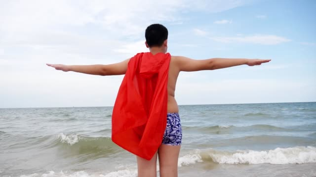 happy superhero wearing face mask with a red cloth shawl having fun on the beach, slow motion and new normal concept. - shawl stock videos & royalty-free footage