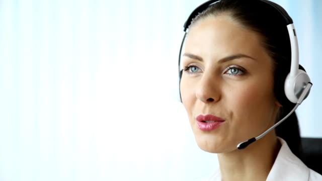 vidéos et rushes de heureux opérateur de téléphonie de soutien de travail - accueil entreprise