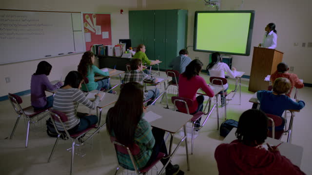 Teacher uses Smart Board in classroom of students