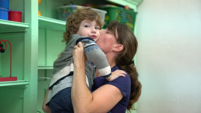 happy teacher kissing and embracing cute boy - child care stock videos & royalty-free footage