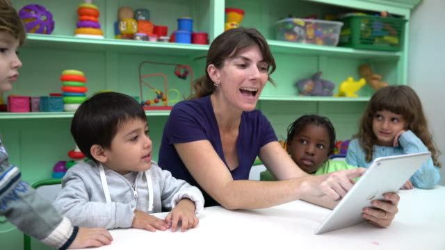 happy teacher narrating story with digital tablet - preschool child stock videos & royalty-free footage