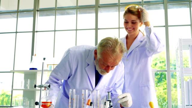glada team medicinsk forskning forskare i laboratorium - läkemedelsfabrik bildbanksvideor och videomaterial från bakom kulisserna