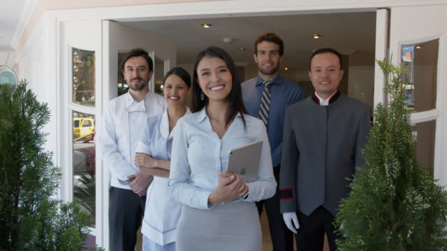 happy team of latin american workers at a hotel facing camera smiling - building entrance stock videos & royalty-free footage