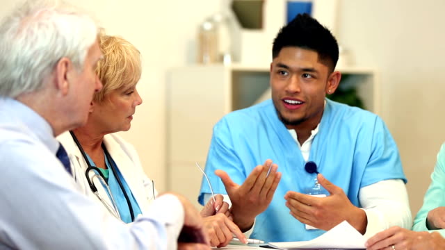 Happy team of nurses and doctors at table having discussion