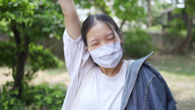 vídeos de stock e filmes b-roll de happy teenage asian woman feeling happy behind the face mask doing v sign and arm raised - 18 19 anos