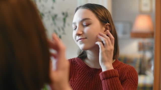 vidéos et rushes de jeune adolescente heureuse regardant dans le miroir - cheveux blanc