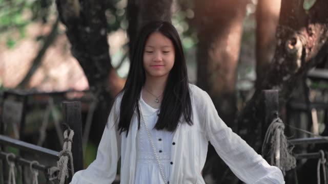 vidéos et rushes de le sourire heureux d'adolescente se détendent en plein air - une seule adolescente