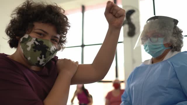 happy teenager boy celebrating after taking vaccine - wearing face mask - epidemiology stock videos & royalty-free footage