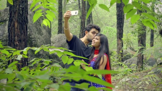 Happy teenager couple taking selfie in park.