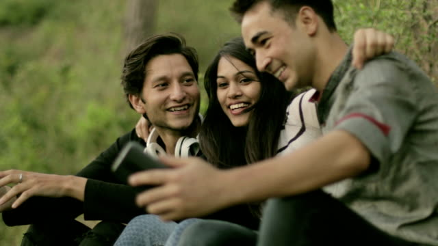 happy teenager friends sitting together and taking selfie - three quarter length stock videos & royalty-free footage