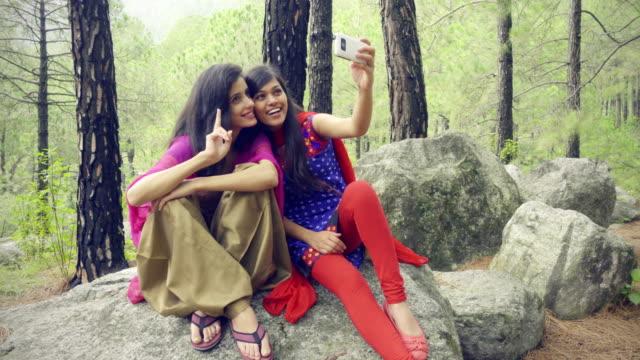 Happy teenager friends taking selfie in park.