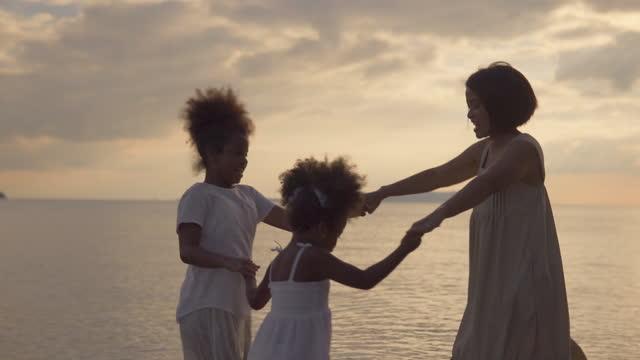 stockvideo's en b-roll-footage met de gelukkige thaise gemengde familie loopt op het zandige strand tijdens zonnige de zomerdag. - sunny