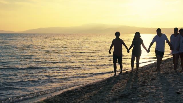 stockvideo's en b-roll-footage met gelukkig drie kind familie loopt langs het strand, in de buurt van zee bij zonsondergang - familie met drie kinderen