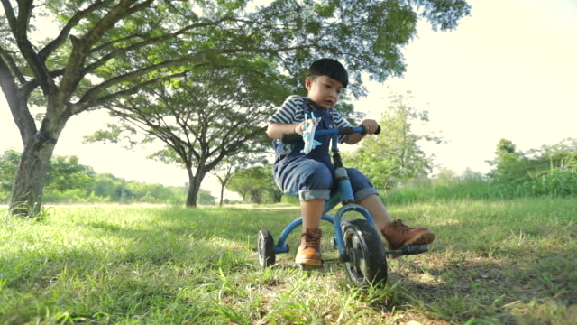 happy time, child playing airplane model in the park with cycling , concept child dream, slow motion - tricycle stock videos & royalty-free footage