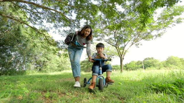 happy time, mother helping little boy ride tricycle in the park, slow motion - tricycle stock videos & royalty-free footage