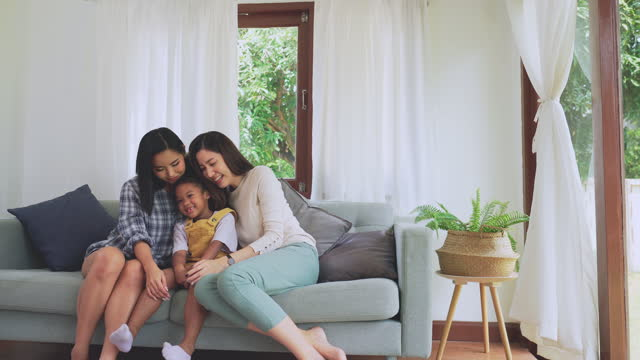 lycklig tid av asiatisk hbtq-familj på soffan adopterar kvinnopar afrikanska dotter, tonårsflickor som modern familj som tillbringar helgtid tillsammans, att behöva le med tandlös, känna sig glad, kramas och positiva känslor tillsammans i hemmet. - enbarnsfamilj bildbanksvideor och videomaterial från bakom kulisserna