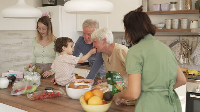 happy toddler boy, feeding his grandparents with a cracker, while all together preparing brunch for a family gathering - weekend activities stock videos & royalty-free footage