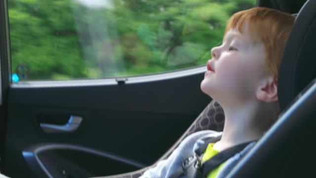 stockvideo's en b-roll-footage met gelukkig peuter jongen zorgen voor op autostoel op road trip - comfortabel