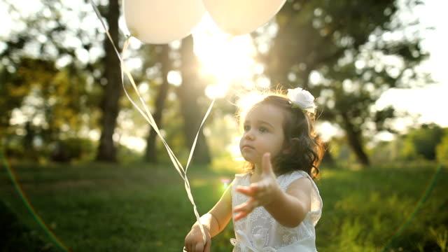 vídeos y material grabado en eventos de stock de chica niño feliz jugando con globos. retrato de una chica sonriente en la naturaleza - globo de helio