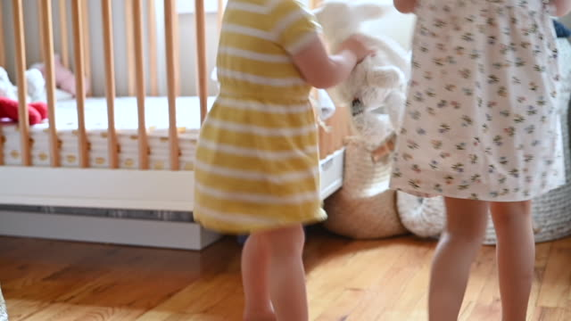 vidéos et rushes de happy toddler sisters dancing and playing together in nursery - tout petit