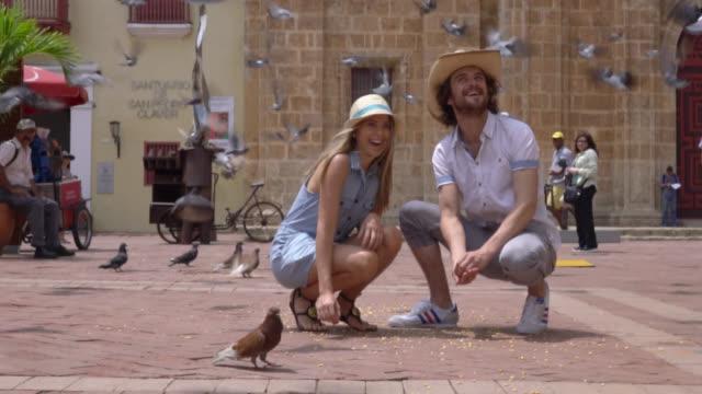 Happy tourist couple feeding the pigeons