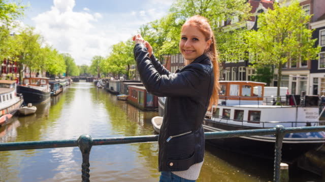 vídeos de stock e filmes b-roll de happy tourist in amsterdam, standing on bridge over canal full of houseboats, photographing with smartphone - barco casa