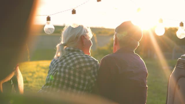 glückliches reisendes paar sitzt im auto offenen kofferraum und kommunizieren bei sonnenaufgang - älteres paar stock-videos und b-roll-filmmaterial