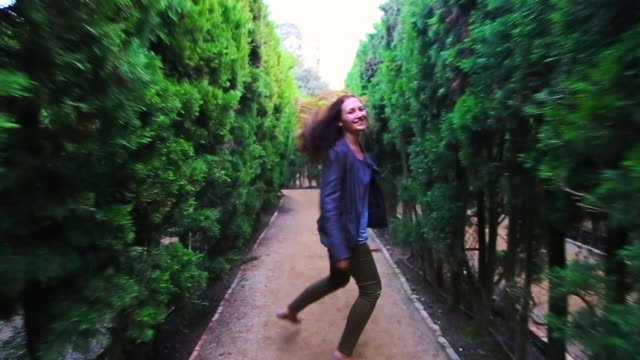 stockvideo's en b-roll-footage met happy traveler girl enjoying visiting gardens with maze in the barcelona city during travel vacations in autumn, running and laughing looking at camera with hair in motion. - doolhof