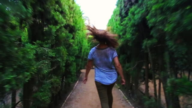 happy traveler girl enjoying visiting gardens with maze in the barcelona city during travel vacations in autumn, running and laughing looking at camera with hair in motion. - maze stock videos and b-roll footage