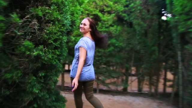 happy traveler girl enjoying visiting gardens with maze in the barcelona city during travel vacations in autumn, running and laughing looking at camera with hair in motion. - maze stock videos & royalty-free footage